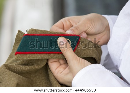 Girl soldier sew a buttonhole on a shirt