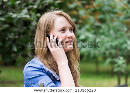 girl speaks by phone in the park - stock photo