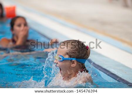 girl splashing in the pool, summer day - stock photo