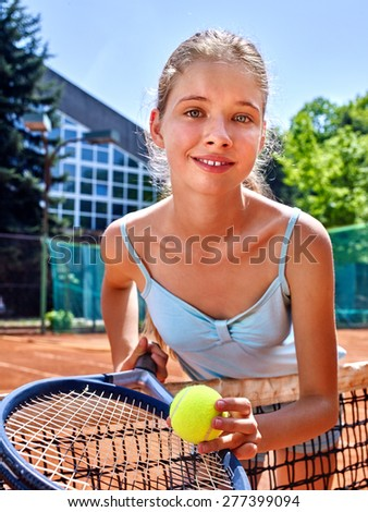Girl sportsman with racket and ball near net on  tennis court. Green tree ang blue sky on background. Looks over her shoulder. Stadion on background. - stock photo