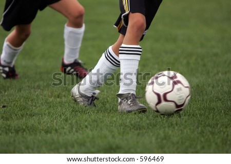 Girl sprints past competitor during a soccer game with ball. - stock photo