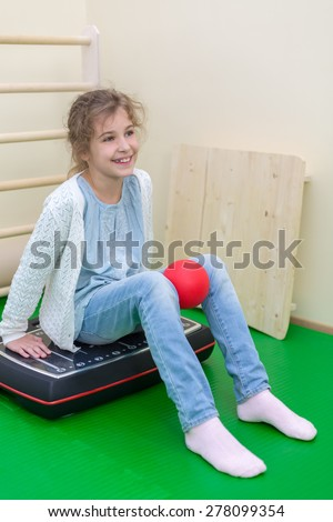 girl squeezes the ball knees seating on vibroplatform - stock photo