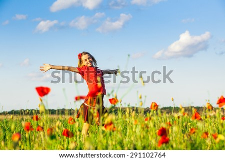 Girl stand with arms outstretched in the poppies field and enjoy the nature - stock photo