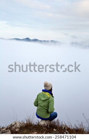Girl standing above the fog - stock photo