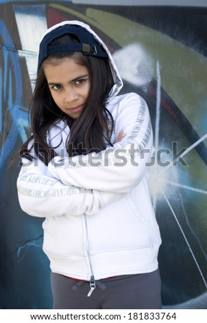 Girl standing against graffiti wall - stock photo