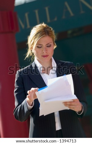girl standing alone in Milan while reading some stuff - stock photo