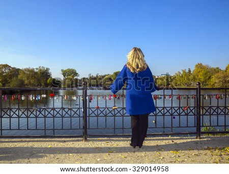 Girl standing alone on a bridge near the lake in the park. - stock photo
