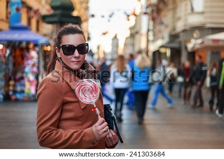 Girl standing and holding a lollipop in the city - stock photo