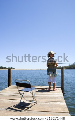 Girl standing at edge of jetty, fishing in lake, rear view - stock photo