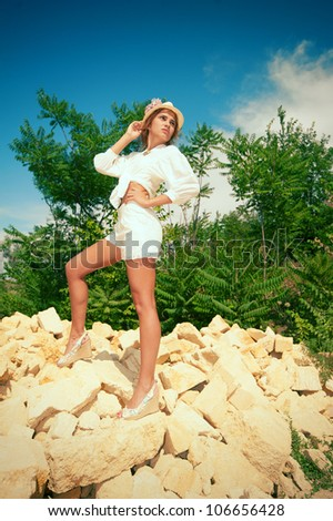 Girl standing at the yellow bricks in sunny summer day - stock photo