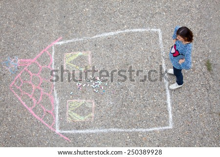 Girl standing beside a drawn house - stock photo