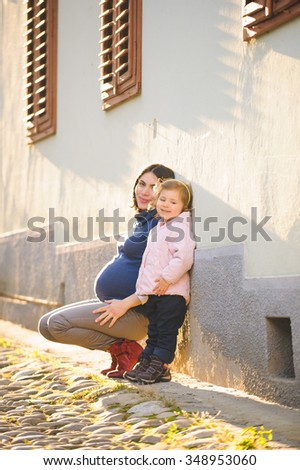 girl standing close to her pregnant mother at wall - stock photo
