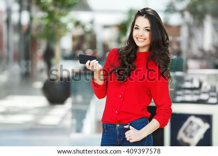 Girl standing in shopping mall, looking at camera and smiling. Beautiful girl holding phone in one hand and another hand on jeans. Wearing red blouse and jeans. Indoor, incidental people - stock photo