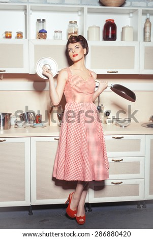 Girl standing in the kitchen in the hands holding a pan and cover. She dreams of cooking. - stock photo