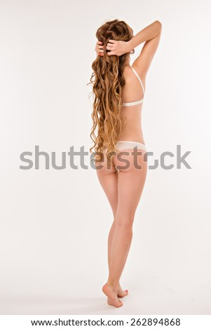 girl standing in white underwear. girl showing slim and toned body and her long hair - stock photo