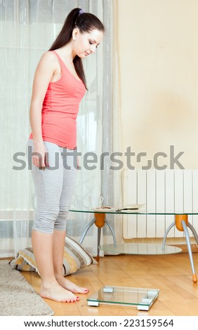 girl standing near  bathroom scales at home interior - stock photo