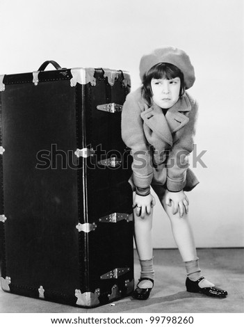 Girl standing next to suitcase