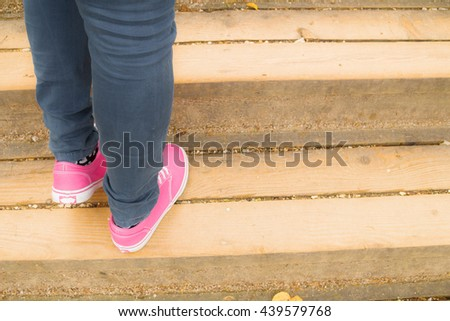 Girl standing on a wooden stairs.