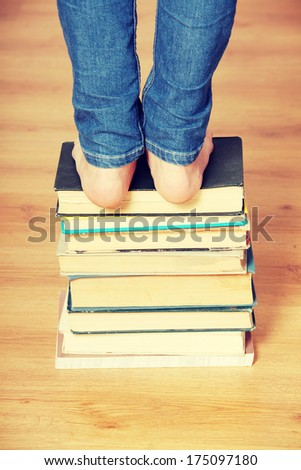 Girl standing on pile of books - stock photo