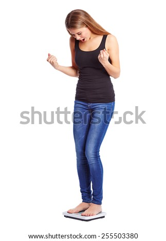 Girl standing on scale weight is happy - stock photo