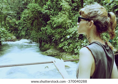 girl standing on suspension bridge and looking at river