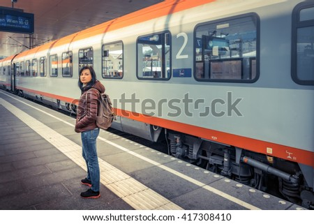 Girl standing on the platform at the train wagon. Traveling by train at the Alpine Railroad