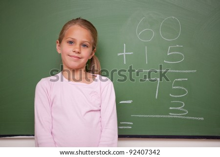 Girl standing up  in front a blackboard - stock photo