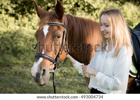 Girl standing with a horse in the forest. Portrait of a young girl with the brown horse