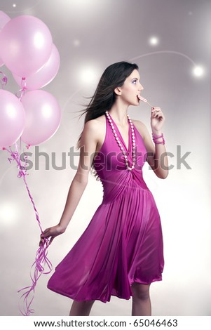 Girl standing with balloons and lollipop