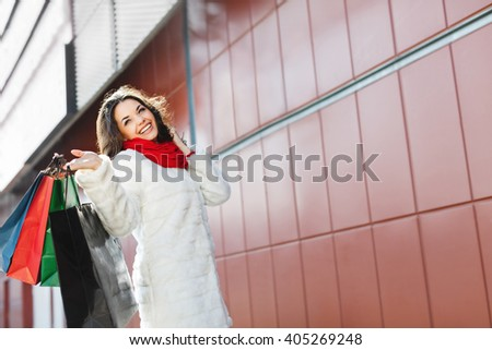 Girl standing with colorful shopping bags near shopping mall and smiling. Beautiful girl with one hand raised holding all bags in it. Putting her another hand on hair. Wearing white coat and red scarf - stock photo