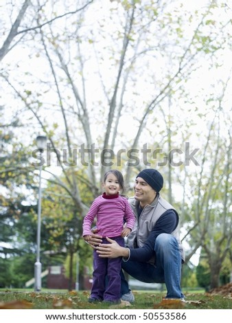 Girl (3-4) standing with father, squatting, in park - stock photo