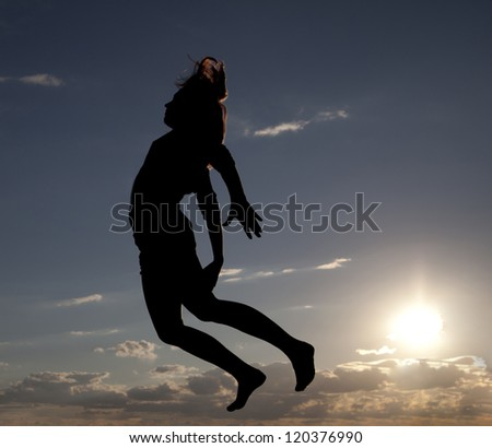 Girl stands in the wind, watching the sunset. energetic woman jumping up to the setting sunlight. Free as a bird
