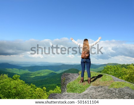 Girl stands on a top of the mountain with his hands up looking at beautiful summer mountain landscape during his hiking trip. .Copy Space. Near Asheville, Blue Ridge Mountains, North carolina, USA.