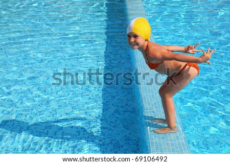 Girl stands on skirting in  pool and prepares to jump in water - stock photo