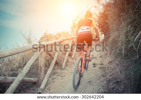 girl stands up to pedal along a steep climb. a ride to a woman in the hills in close contact with nature. Cyclist pedaling uphill with a backdrop of the sea at sunset. - stock photo