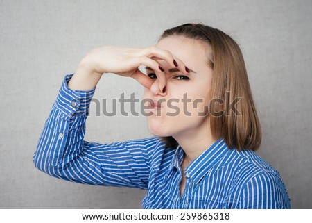 girl stinks and she closed her nose with his hand - stock photo