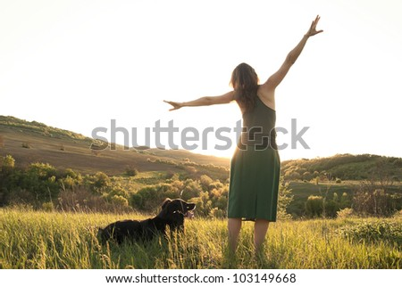 Girl stretches in the sunlight whilst walking her dog - stock photo