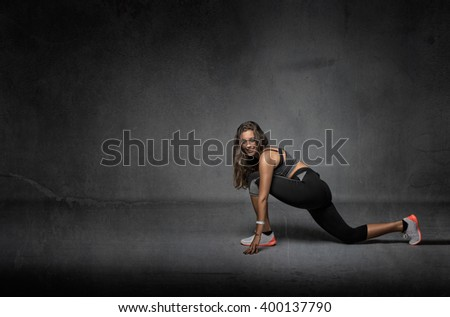 girl stretching after fitness, dark background - stock photo