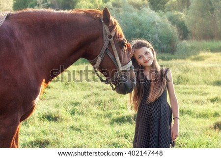 Girl stroking her horse and looking at the camera on the sunlit field