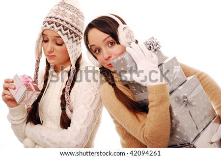 Girl struggling with large stack of presents and girl with tiny present on white background - stock photo