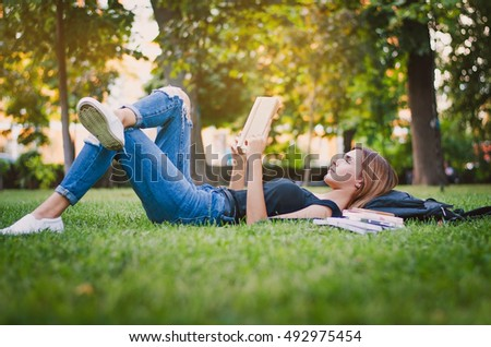 girl student in a park lying on the grass and reading a book, lying next to her backpack and a stack of notebooks. Education concept