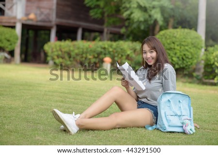 Girl student read a book in public park