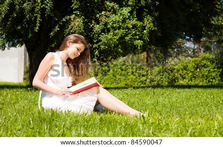 Girl-student sit on lawn and reads textbook