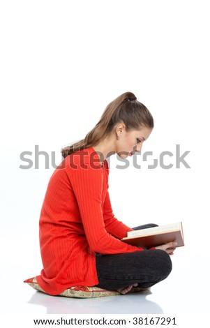 girl student sits and reads book on white background - stock photo