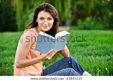 Girl-student sits on lawn and reads textbook.