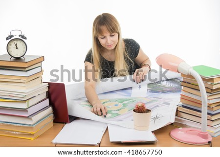 Girl student studying design drawing master plan at a table cluttered with books - stock photo