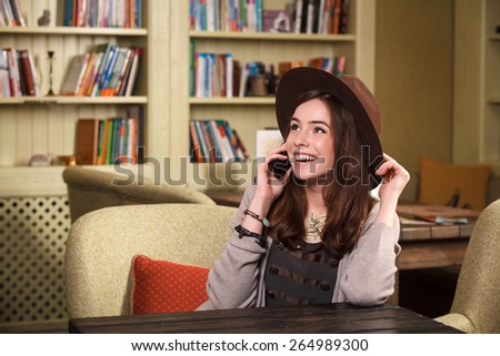 girl student talking on the phone in a cafe, university. Young woman talking on the phone in a cafe - stock photo
