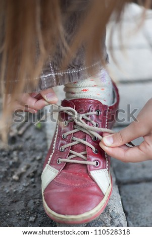 girl successfully ties shoes - stock photo