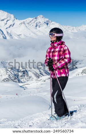 girl sunbathing near a snowy ski slope with blue sky background