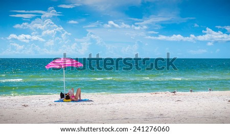 Girl sunbathing under pink umbrella on St. Pete beach in Florida, USA - stock photo